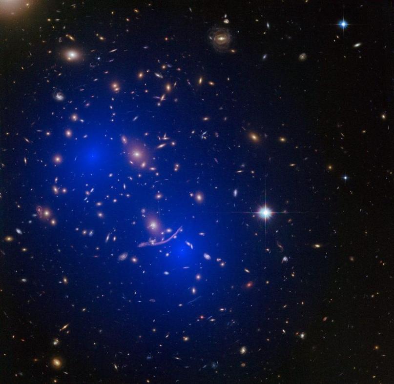 Распределение массы в скоплении галактик Abell 370 воссозданное через гравитационное линзирование, демонстрирует два больших и рассеянных гало массы, соответствующих двум сливающимся скоплениям ТМ.