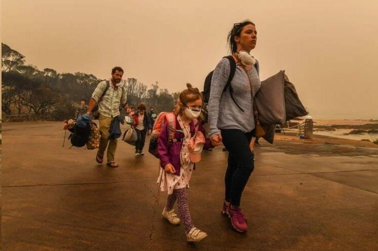 Люди бегут от австралийских лесных пожаров в декабре 2019 года